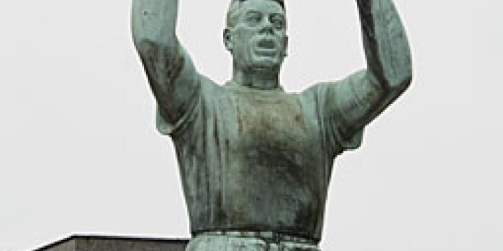 Le monument Julien Lahaut au cimetière de Seraing. Inauguré sous sa forme définitive en 1956, il comporte une statue de l'homme politique dans sa posture familière de tribun et, derrière lui, un monument plus massif symbolisant le 'peuple', que Lahaut paraît protéger. (Photo équipe projet Lahaut, Cegesoma)
